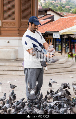 Sarajevo, Bosnia-Herzegovina, July 16 2017: Man feeds pigeons in front of the Sebilj fountain in historical city center - Stock Photo