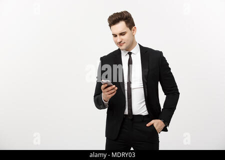 Business Concept: Happy young businessmanman in smart suit typing sms on gray background - Stock Photo