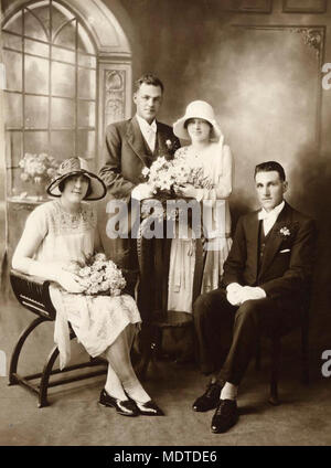 Wedding party, north Queensland, 1920-1930. Studio photograph of a bride and bridegroom with their bridesmaid and best man. The bride and groom are posed behind a carved wooden stand, the bride's bouquet resting on the stand. The bridesmaid and best man are seated in front and to either side of the bridal couple. The bride and bridesmaid wear typical twenties style dresses and hats - Stock Photo
