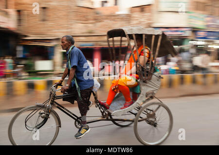 A local rickshaw driver with passenger. - Stock Photo