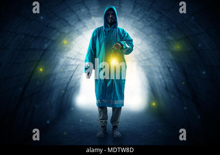 Ugly man in raincoat walking with glowing lantern in a dark tunnel - Stock Photo