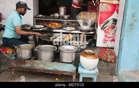 A local Young man preparing his street food before the midday rush. - Stock Photo