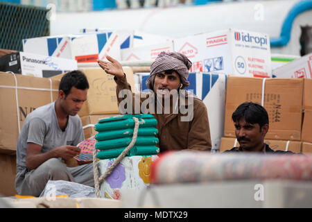 Labourers taking a break from work unloading from a dhow moored along the Dubai Creek, Deira, Dubai, United Arab Emirates, Middle East - Stock Photo