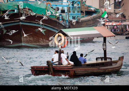 Local people crossing the Dubai Creek on an abra with dhows in the background and seagulls flying behind, Dubai, United Arab Emirates, Middle East - Stock Photo