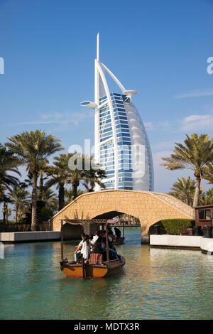 Tourists riding on an abra on the waterways of the Madinat Jumeirah with the Burj Al Arab behind, Dubai, United Arab Emirates, Middle East - Stock Photo