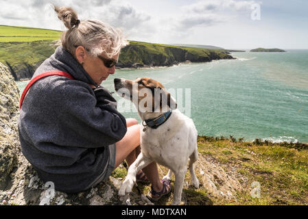 Walking the dog on Foel y Mwnt with Ceredigion coast and Cardigan Bay in the background - Stock Photo