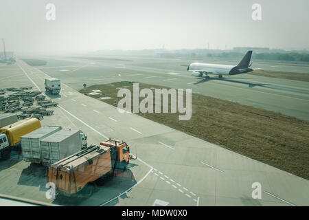 A passenger plane being serviced by ground services before next takeoff. pushback tug, passenger boarding steps vehicle, tractor with baggage carts an - Stock Photo