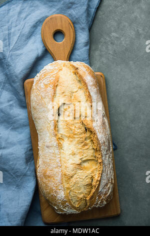 Freshly Baked Hand Crafted Rustic Bread Loaf on Cutting Board Dark Stone Background. Authentic Rustic Style. Lifestyle. Mediterranean Cuisine. Food Ba - Stock Photo