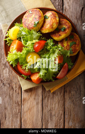 Freshly prepared potato pancakes are served with fresh salad close-up on a plate. Vertical top view from above - Stock Photo