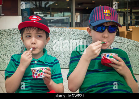 Young boys sit together eating tubs of ice cream - Stock Photo