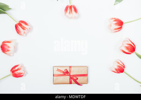 Top view frame made of golden gift box with red ribbon and tulip flowers around on white background. Floral flat lay composition with blank space in c - Stock Photo