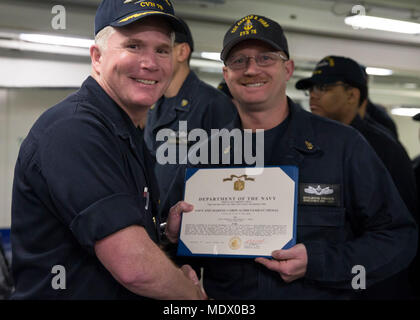 ATLANTIC OCEAN (Dec. 13, 2017) --  Chief Boatswain's Mate Benjamin Hansen, assigned to USS Gerald R. Ford's (CVN 78) deck department, receives a Navy and Marine Corps Achievement Medal from Capt. Richard McCormack, Ford's commanding officer, during an awards at quarters in the ship's forecastle. Ford is underway conducting test and evaluation operations. (U.S. Navy photo by Mass Communication Specialist 3rd Class Cat Campbell)