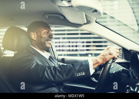 African businessman wearing a blazer and smiling while driving his car through the city during his morning commute to work - Stock Photo