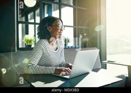 Smiling young African woman wearing glasses looking out of a window while sitting at a table working online with a laptop - Stock Photo