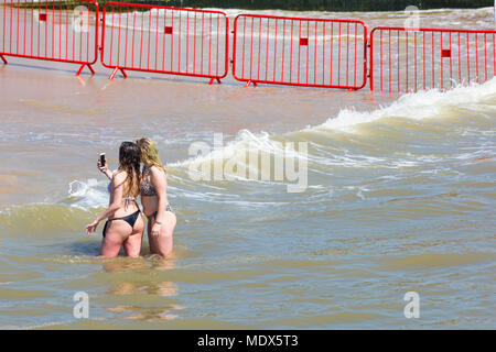 Bournemouth, Dorset, UK. 20th April 2018. UK weather: beaches are crowded as visitors flock to the beach to enjoy the hot sunny weather at Bournemouth. Two young women having fun taking selfies in the sea. Credit: Carolyn Jenkins/Alamy Live News - Stock Photo