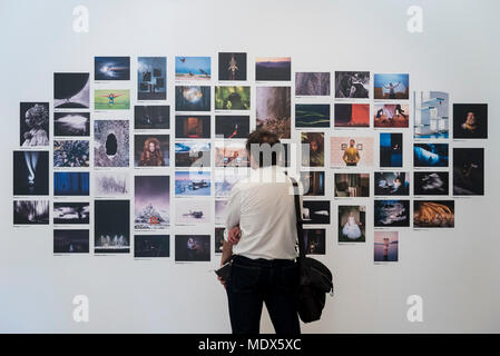 London, UK.  20 April 2018. A visitor views a montage of images at the 2018 Sony World Photography Awards Exhibition at Somerset House.  The 11th edition of the competition saw 320,000 submissions from over 200 countries.  The exhibition runs 20 April to 6 May.  Credit: Stephen Chung / Alamy Live News - Stock Photo