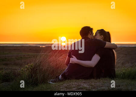 Stunning Sunset, Southport, Merseyside. 20th April 2018. UK Weather.  A young romantic couple sneak a loving kiss as a spectacular sunset nestles into the horizon after a beautiful spring day in Southport, Merseyside. Credit: Cernan Elias/Alamy Live News - Stock Photo