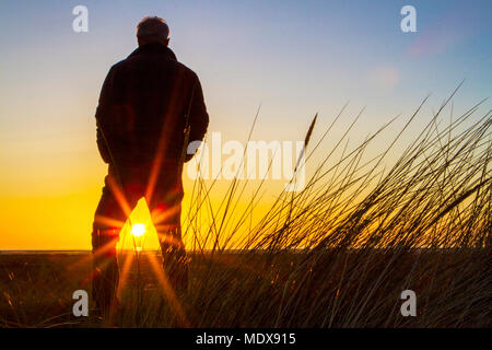 Stunning Sunset, Southport, Merseyside. 20th April 2018. UK Weather. A man stands on the sand dunes watching as the sunset drops into the horizon over Southport beach in Merseyside.  Credit: Cernan Elias/Alamy Live News - Stock Photo