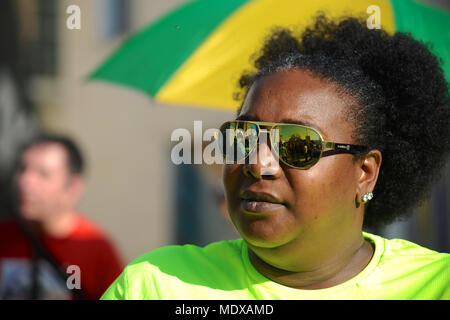 London, UK. 20th April, 2018. The Windrush Generation Solidarity demonstration reflected in the sunglasses of a woman, London, United Kingdom.  The demonstration was called in response to the Home Office's incompetence and  bureaucratic brutality towards the Windrush generation.  The Windrush generation refers to the workers from Jamaica, Trinidad and Tobago and other islands who arrived in London between 1948 and 1971 as a response to post-war labour shortages in the UK. Credit: Michael Preston/Alamy Live News - Stock Photo