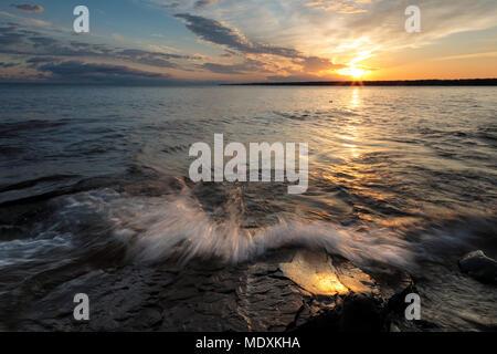 Sunrise illuminates a rocky Lake Superior shoreline as a wave crashes over sandstone. Dramatic clouds light the early morning sky - Stock Photo