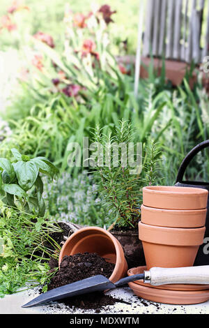 Rustic table with terracotta pots, potting soil, trowel and herbs in front of a beautiful garden surrounding a rustic porch. - Stock Photo