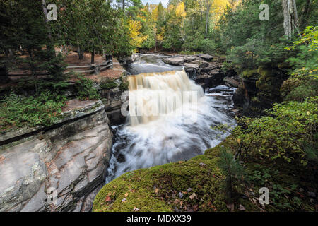 The Sturgeon River flows rapidly over Canyon Falls near L'Anse Michigan. Autumn colors in the background. Known as Michigan's Grand Canyon - Stock Photo