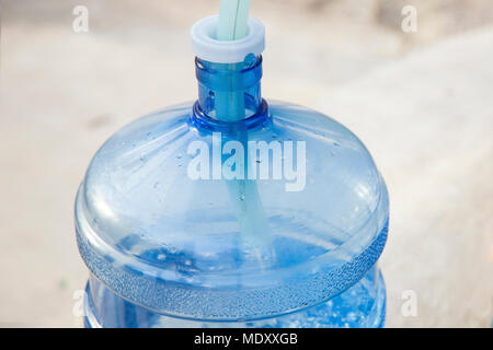 Water Gallon Refill Vending Station pump (gallon) for water with a hose inside at the time of filling in close up, background image - Stock Photo