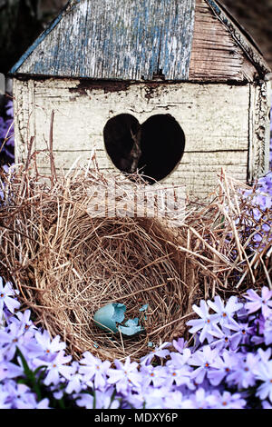 Broken blue egg lying in a nest in front of an old rustic bird house. - Stock Photo