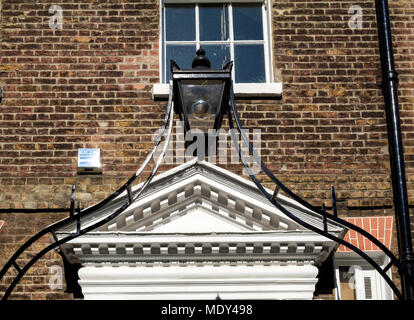 Old ornate wrought iron street light in front of brick building at St. Pancras, Central London. - Stock Photo