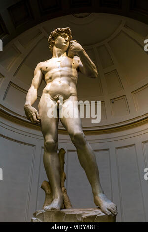 Full-length of 'Michelangelo's David' sculpture with dome in the background; Florence, Tuscany, Italy - Stock Photo