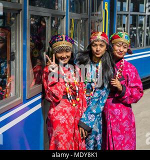 Three women wearing kimonos pose outside the Darjeeling Toy Train, Darjeeling Himalayan Railway; Darjeeling, West Bengal, India - Stock Photo