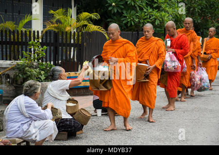 Buddhist monks receiving alms on Khounsua Road at dawn; Luang Prabang, Luang Prabang, Laos - Stock Photo