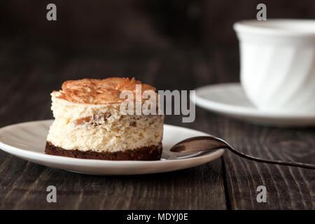 Tiramisu cake on a white saucer and a cup of black coffee - Stock Photo