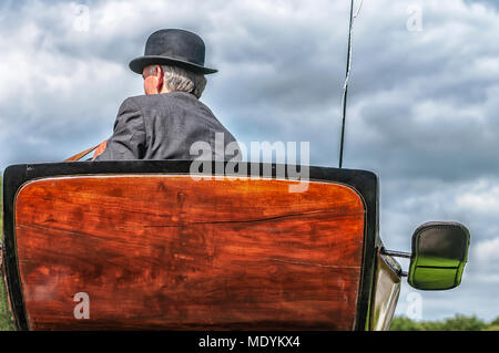 riding a horse-drawn carriage with a bowler hat on his head - Stock Photo