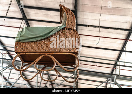 large wicker pram hangs from the ceiling - Stock Photo