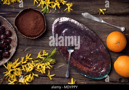 flatlay empty food background with empty plate, oranges, chocolate, yellow flowers, fork and knife on wood board, with copy space for text - Stock Photo