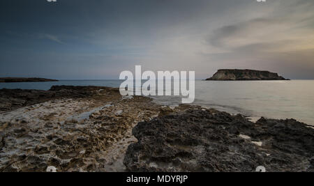 Rocky Seascape at dramatic sunset with the small  island of Geronisos at Paphos area Akamas peninsula in Cyprus - Stock Photo