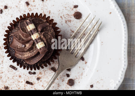 Chocolate cupcake on white plate with fork, dusted with cocoa powder and chocolate sprinkles, Overhead View - Stock Photo