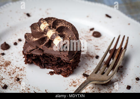 Chocolate cupcake on white plate with fork, dusted with cocoa powder and chocolate sprinkles, half eaten - Stock Photo