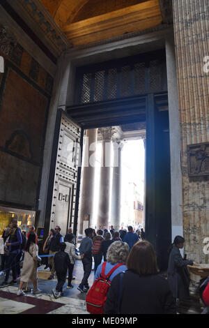 Tourists exit through the large bronze doors from the 15th century. The Pantheon is a former Roman temple, now a church, in Rome. The present building - Stock Photo