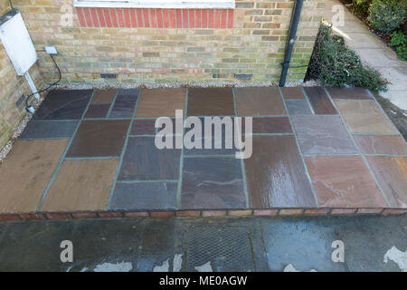 A new patio made with stone slabs, with water on it to wet the drying mortar / cement as it cures – dries – built in the front garden of a small house - Stock Photo