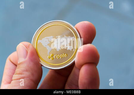 Silver gold ripple coin in hand, cryptocurrency investing concept - Stock Photo