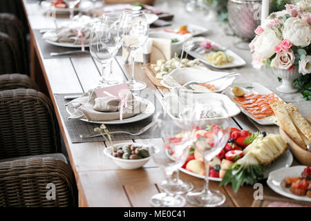 Garland of flowers and greenery for table decoration. Luxury wedding reception in restaurant. Stylish decor and adorning. White candles on glass candl
