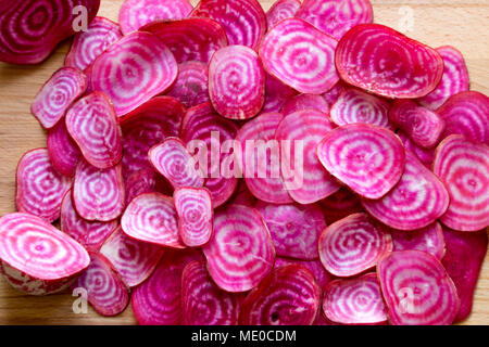 Colourful root vegetables slices.  Sliced organic chioggia beets (candy beetroot) showing their vibrant red and white concentric rings. - Stock Photo