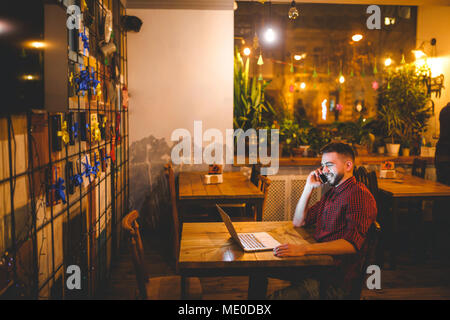 Young handsome Caucasian man with beard and toothy smile in red shirt works behind laptop, hands on keyboard sitting at wooden table. Uses calls on mo - Stock Photo