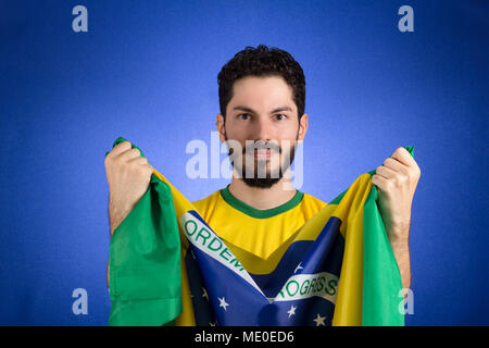 Brazilian soccer football team player. One supporter and fan holding Brazil flag. Wearing yellow uniform on blue backdrop. - Stock Photo