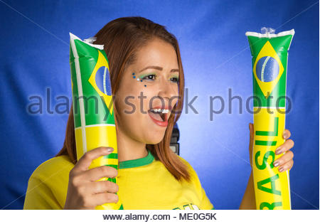 Brazil supporter. Brazilian woman fan celebrating on soccer / footbal match on blue background. Brazil colors. - Stock Photo