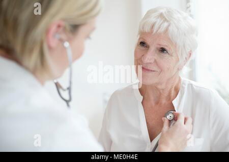 Female doctor examining senior woman. - Stock Photo