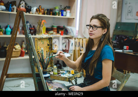 Pretty girl artist paints on canvas in art studio - Stock Photo