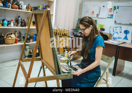Female painter drawing in art studio using easel - Stock Photo